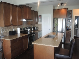 Kitchen with granite countertop, built-in microwave and a walk through pantry to back entrance and the garage