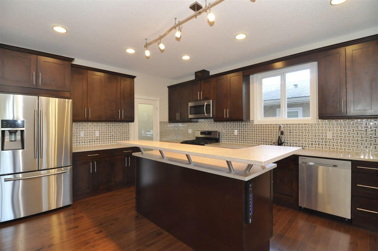 Solid Wood Cabinets With Tall Uppers In This L Shaped Kitchen Having Gleeming Quartz Countertops, Tile Backsplash, Raised Eating Bar, Large Pantry, and Stainless Steel Appliances Featuring A Gas Stove!