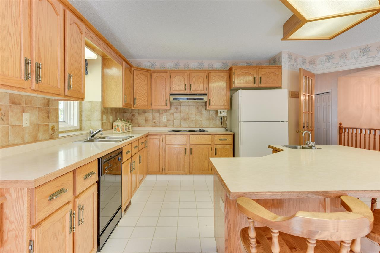 Enormous kitchen has oak cabinets, a large island/breakfast bar and doors leading onto the deck/back yard.