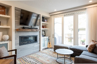 The gas fireplace with tile surround features a custom wood mantle.