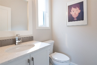 The 2pc main-floor powder room is tucked away for privacy.