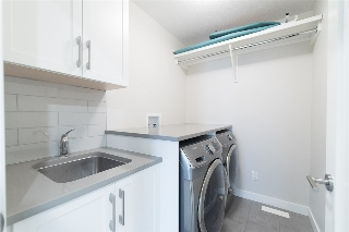 Full sized laundry room has plenty of storage, side by side Samsung appliances with STEAM care and a utility sink (incl. quartz counter top!)