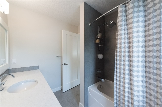 The 4pc main bathroom on the upper level features quartz countertops and a shower/tub combo.