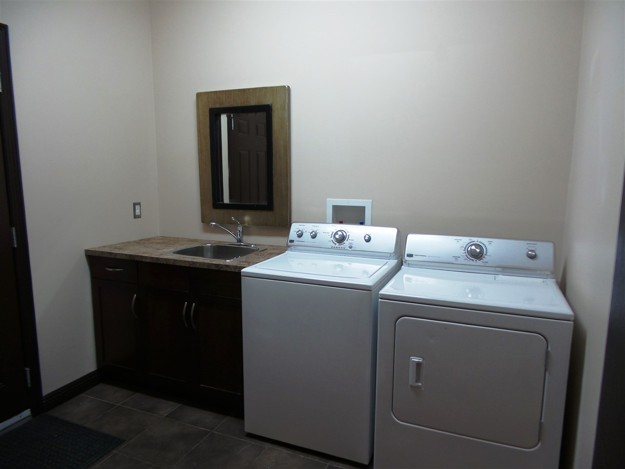 Main floor laundry/mud room with sink and walk in closet