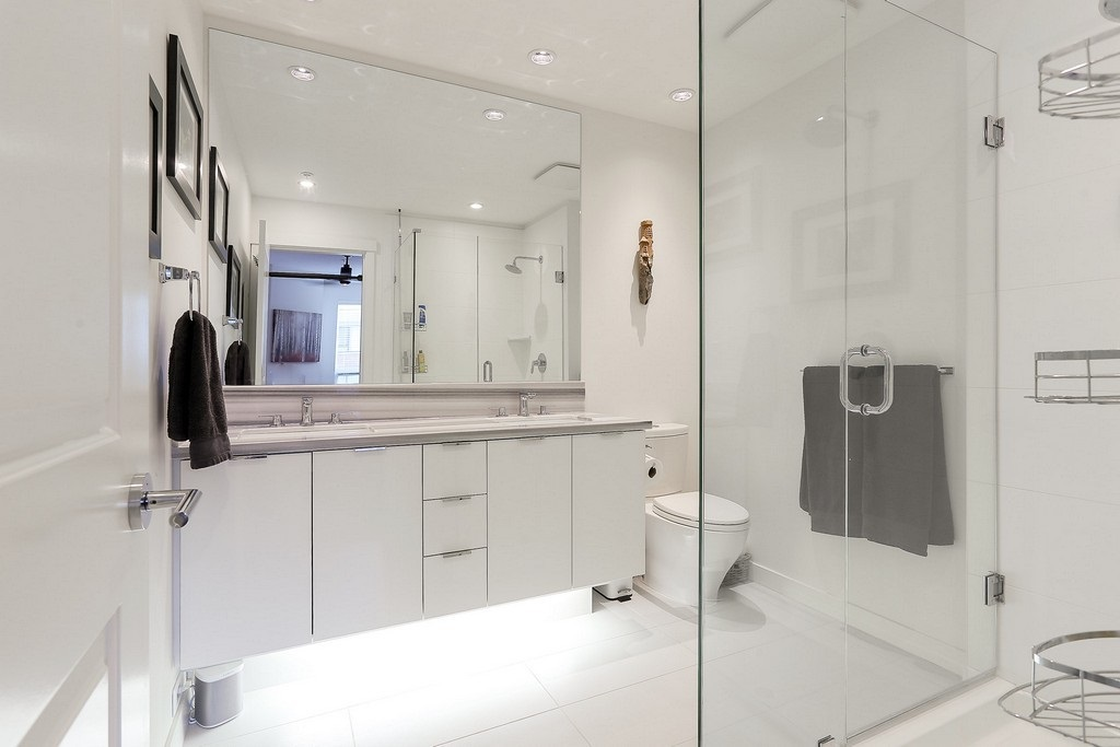 Master bath with under counter lights, 2 sinks and large glass shower.