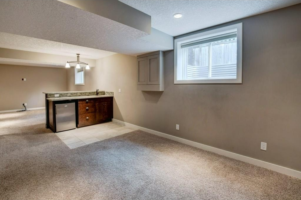Bright and modern basement with newer carpets. Raised wet bar complete with granite countertops, mini fridge and sink.