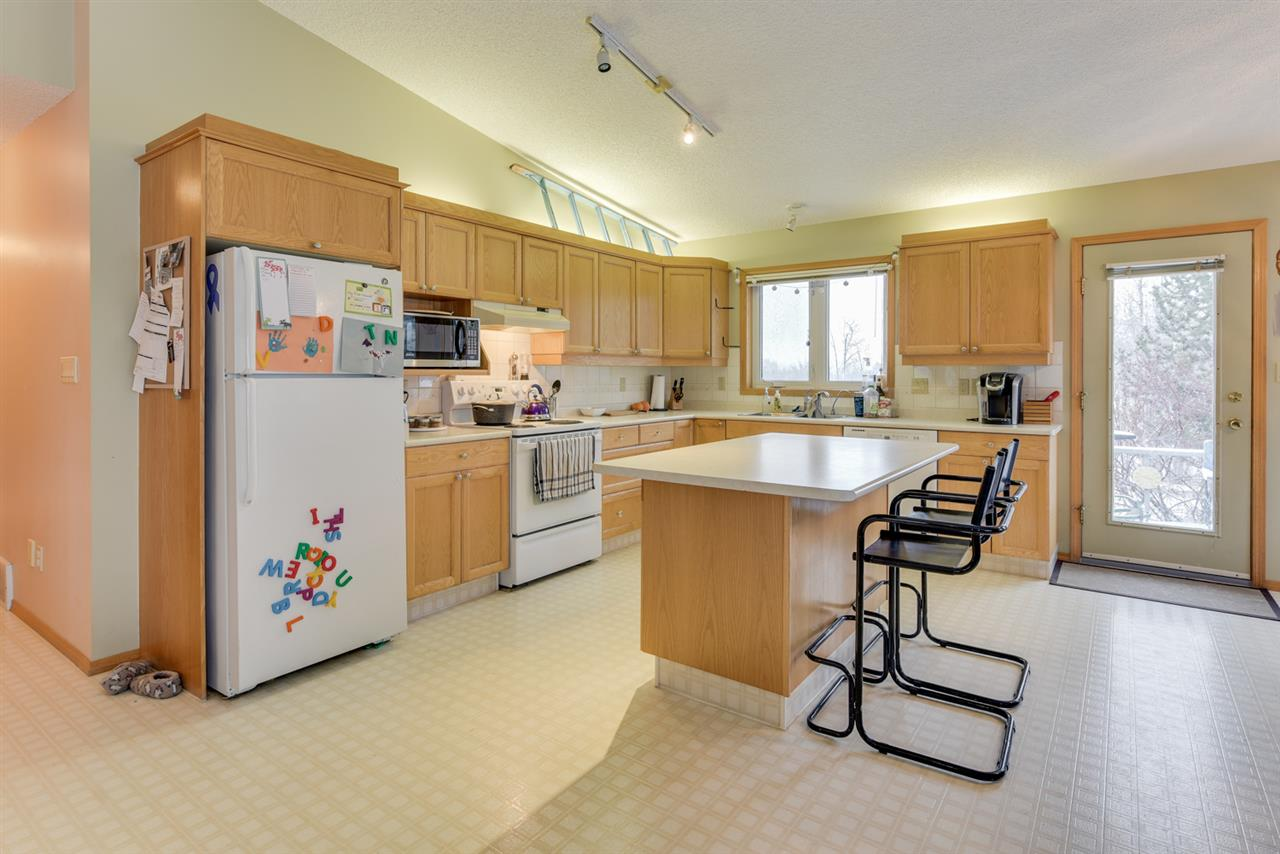 Kitchen features vaulted ceilings, oak cabinets and island kitchen