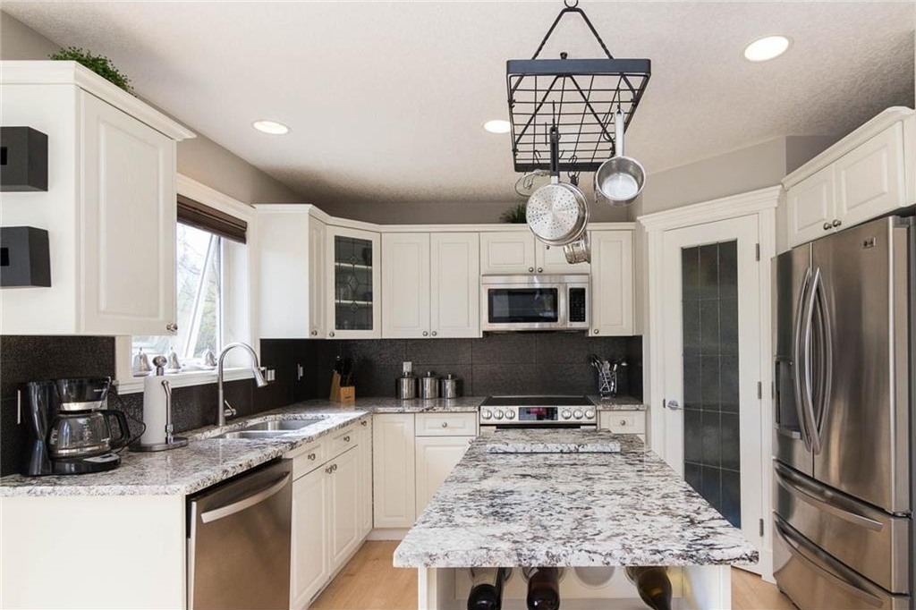 The white kitchen is bright & modern and features granite counters, stainless steel appliances, central island & corner pantry.