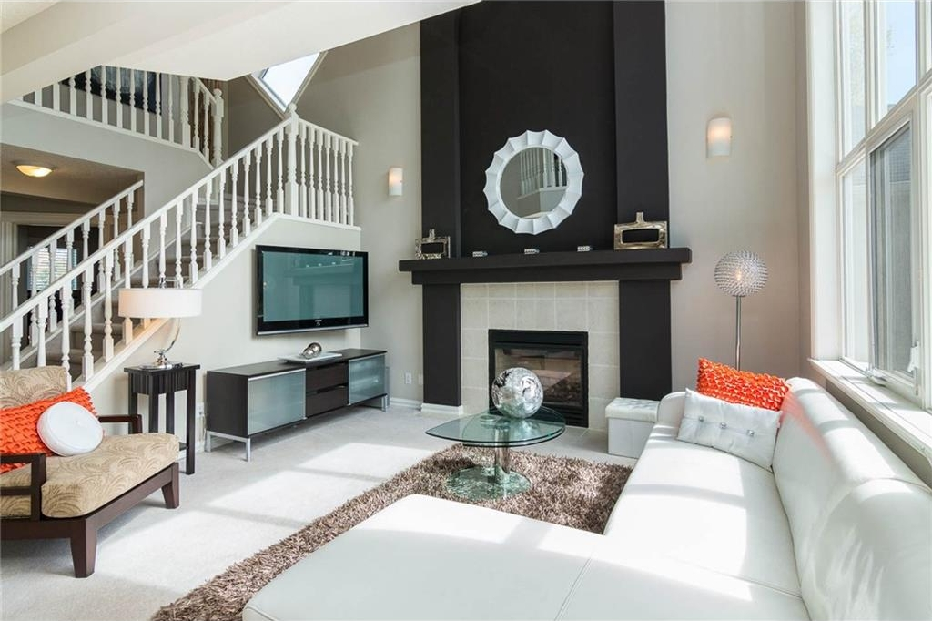 The family room showcases a 2 storey ceiling, wall of windows & feature wall with gas fireplace.