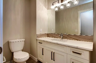 Main bath with gorgeous quartz counters and tasteful modern light fixture