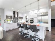 Gourmet kitchen with tile backsplash, quartz countertop, oversized island with eating area.