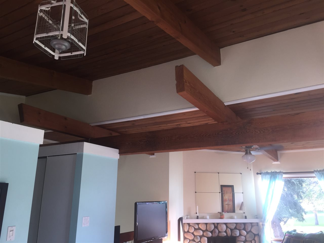Gorgeous wood ceiling with open beams. Open over living room railing to entrance below. Hallway up to left with bathroom and closet.