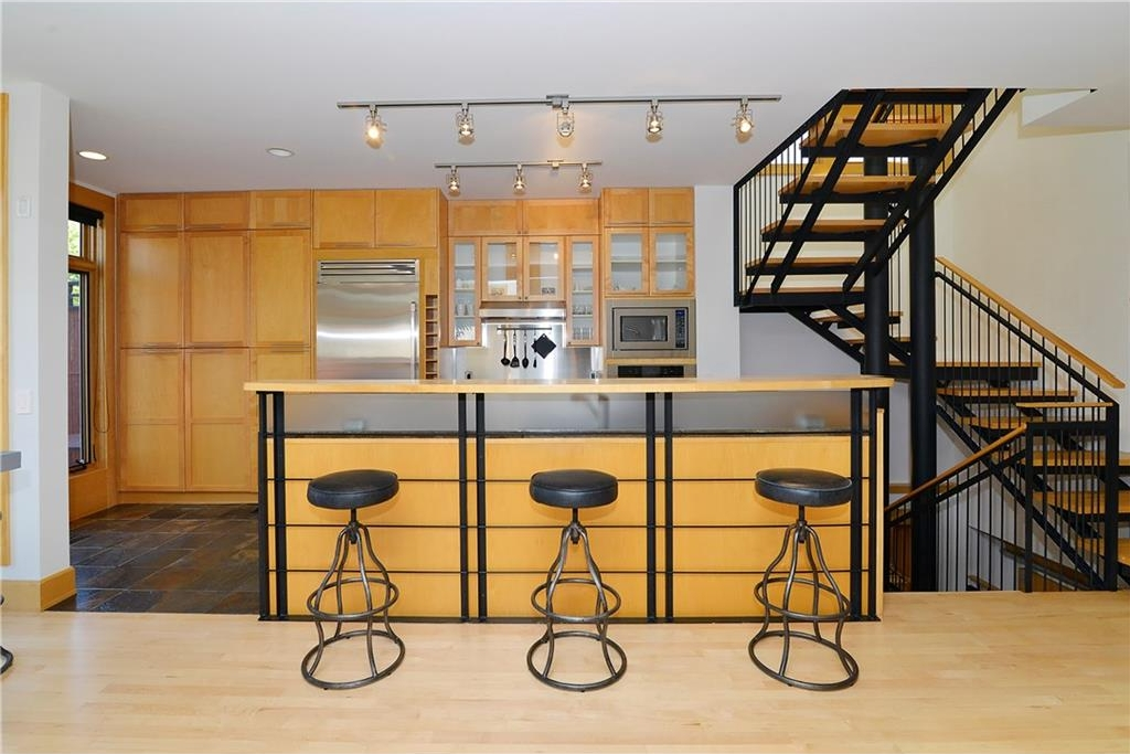 Another view of the kitchen and open-risers staircase.