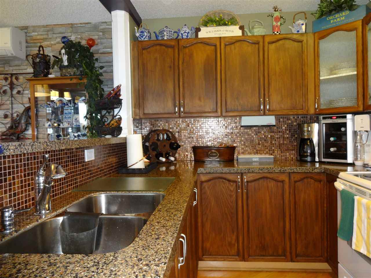 Upgraded Kitchen - stained cupboards, granite countertops, backsplash, glass inserts into cupboards, new taps.