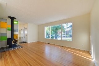 living room features, large window, hardwood floors and wood burning stove.