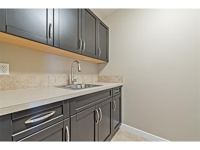 Upper level laundry room with sink and built-in cabinets.