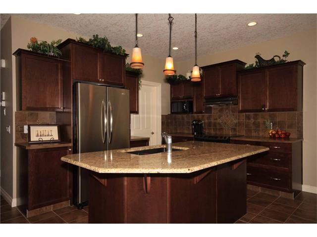 Large kitchen island with a large granite counter top.