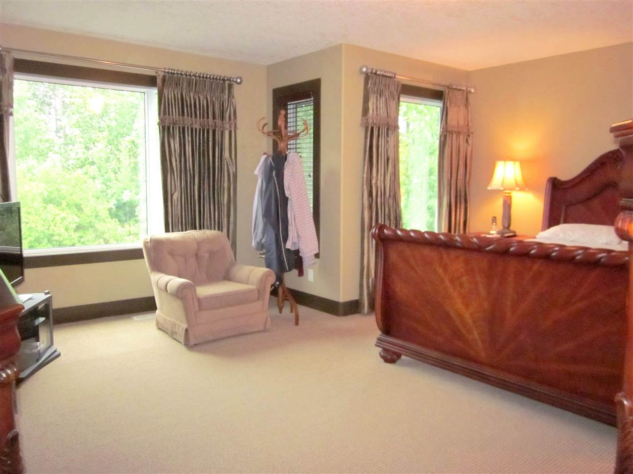Master bedroom has view of the beautifully landscaped backyard and the treed area.