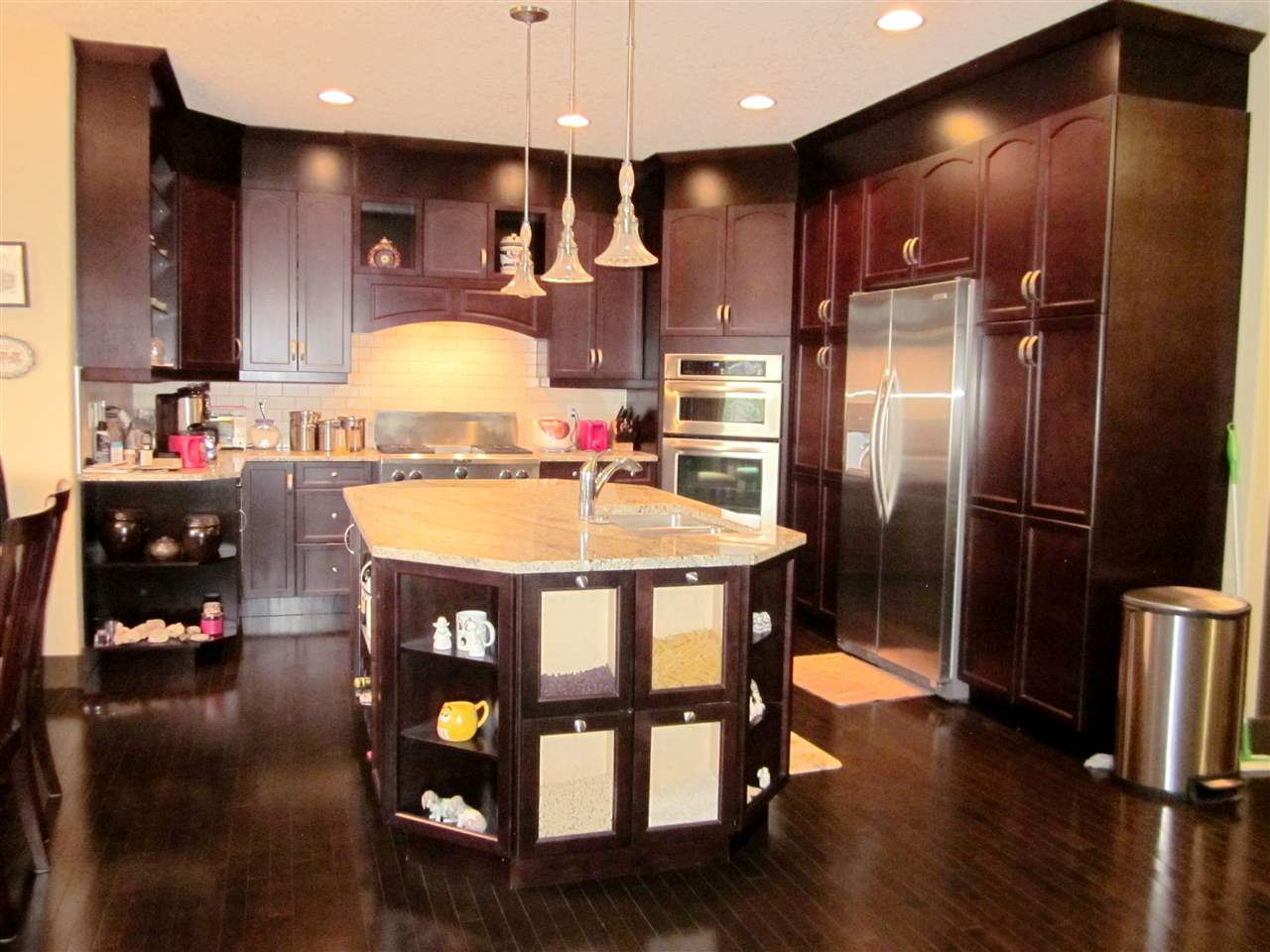Gorgeous kitchen with octagon shape island, granite countertops, ample dark cabinets, high end stainless steel appliances with gas stove, built-in ovens, and tile backsplash.