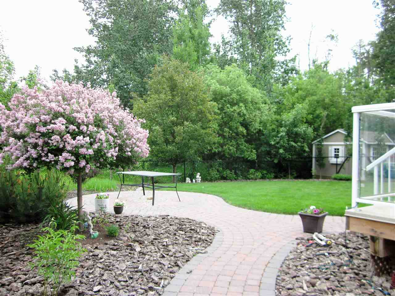Beautifully landscaped backyard with patio and backing onto the treed area.