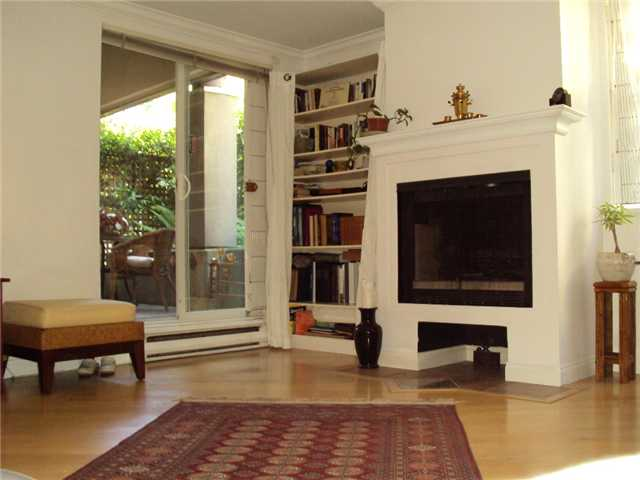 Crown mouldings, laminate flooring, wood burning fireplace are featured in this large Living room
