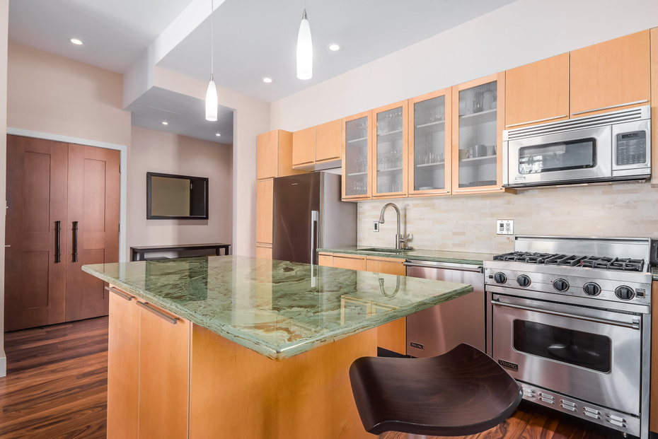 Ample Cupboard and Counter Space, including breakfast bar on either end of stunning green granite countertops.