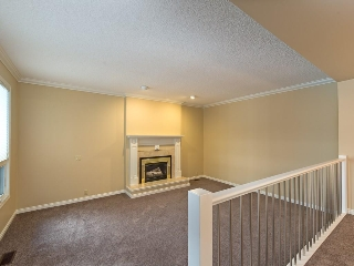 Living room with tile trimmed gas fireplace.