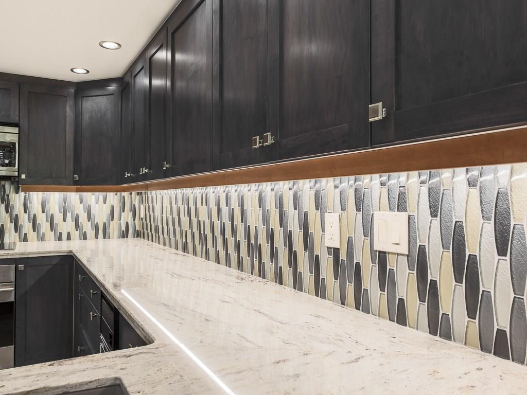 Modern tile backsplash with under cabinet lighting.