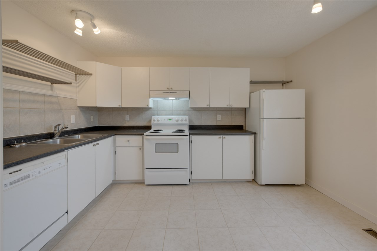 The large kitchen with newer appliances and white cabinets will appeal to any modern tastes.