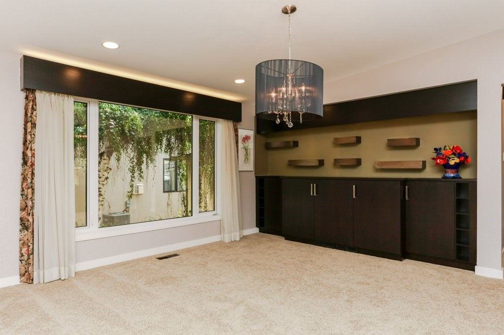 Formal dining room with large window. Custom shelves on back wall.