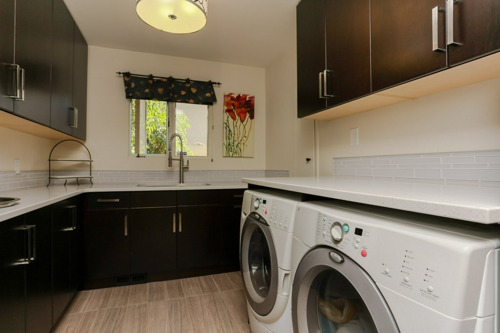Laundry room / butler's pantry has lots of extra storage, counter space plus a laundry sink.