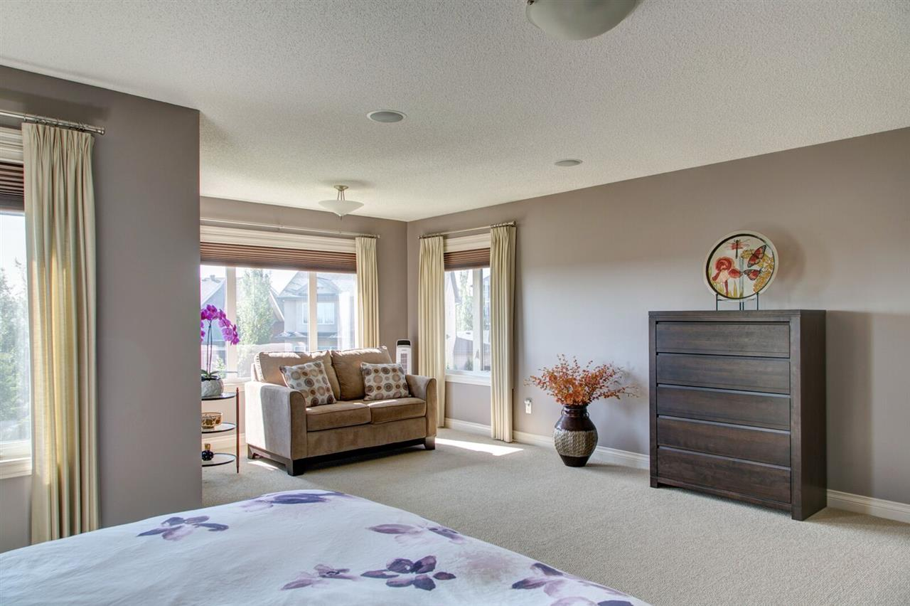 Relax in master bedroom sitting area surrounded by windows.