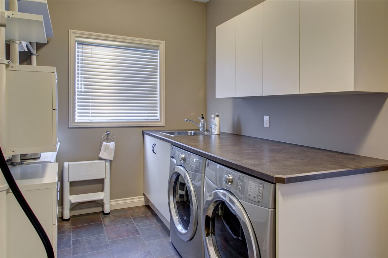 Convenient main floor laundry with utility sink in the mud room.