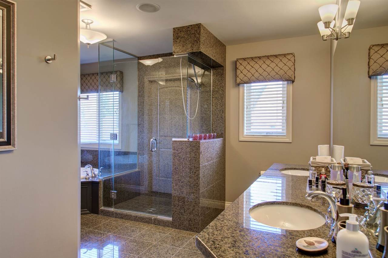 Master spa bath with dual vanities, walk in shower with granite tile surround, soaker tub and walk in closet.