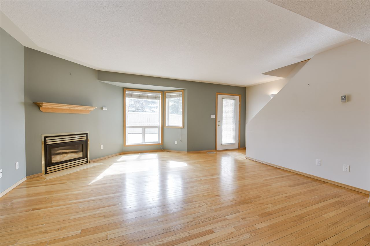 Living room has hardwood flooring, lots of natural light and a gas fireplace
