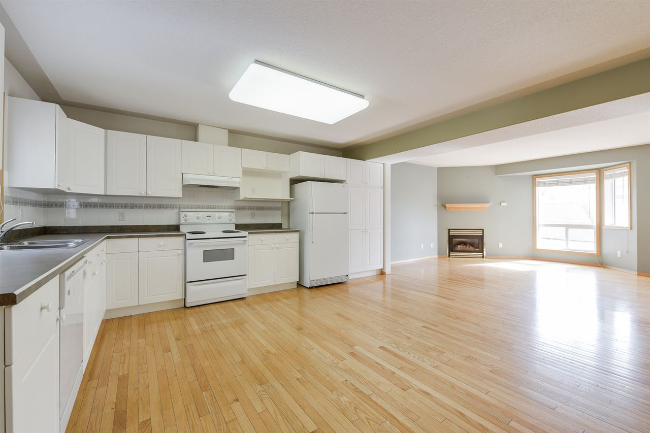 The property features hardwood flooring, oak cabinets and white appliances
