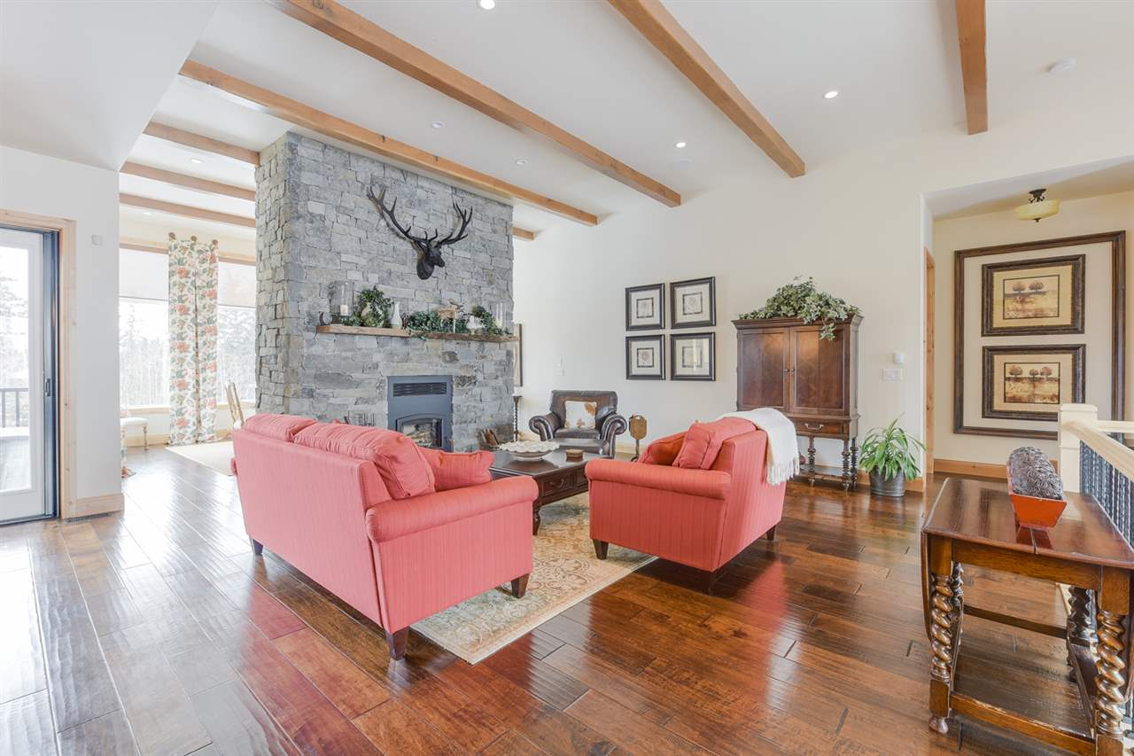 Gorgeous living room/great room featuring 12' or 10' flat ceilings, engineered maple hardwood and a wood burning fireplace.