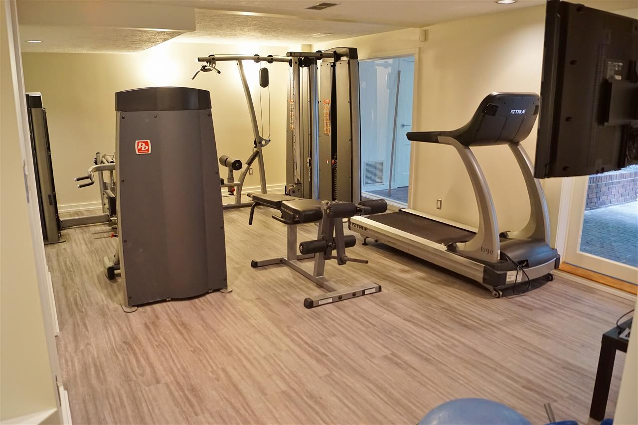 29) Living room in basement set up as exercise room with vinyl plank flooring