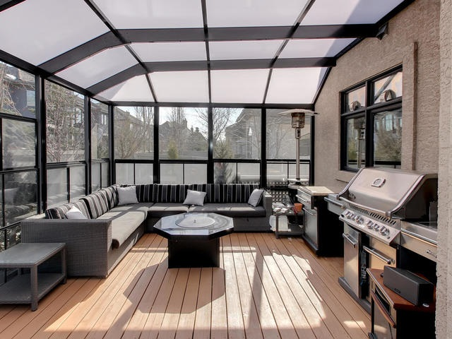 Beautiful enclosed sun room with BBQ and sitting area.
