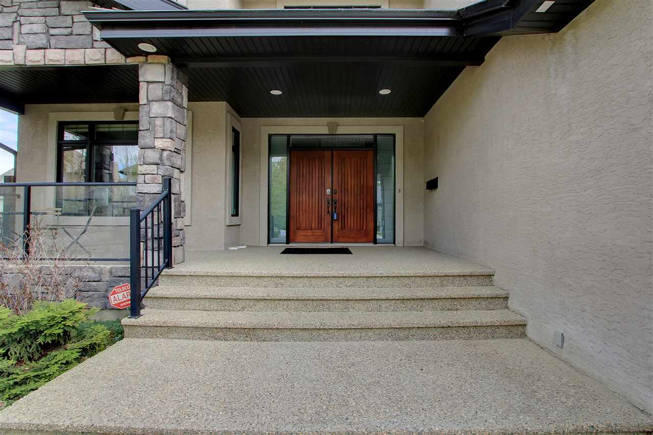Solid maple double doors and expansive aggregate walkway offer a grand entrance.