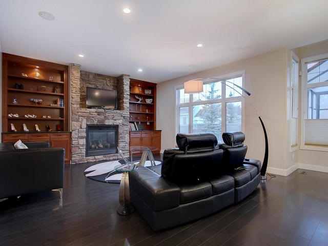 Custom built-in cabinets and shelving frame the floor to ceiling stone gas fireplace.
