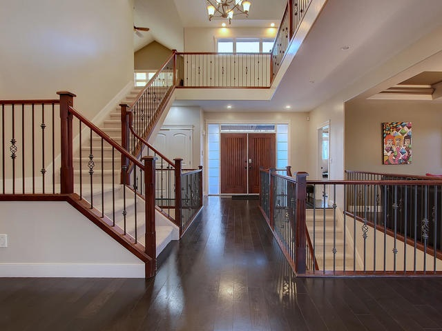 Grand entrance into this beautiful home with open staircase of maple and iron accents flowing from top to lower levels.