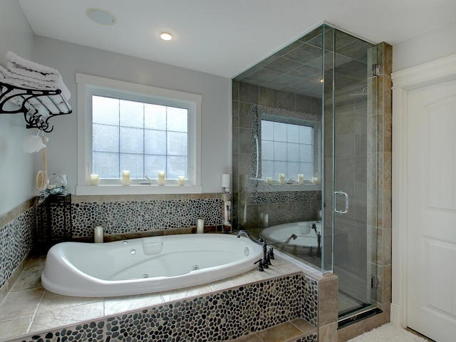 Large soaker tub and separate glass shower along with custom cabinetry and granite counters with 2 His and Her sinks.