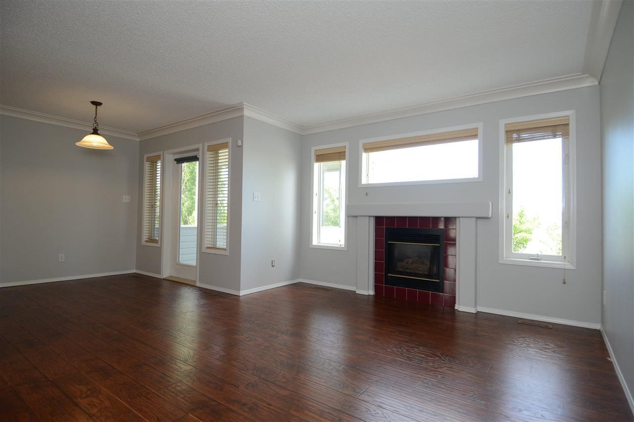 Open concept: dining room, living room, kitchen, and a screened in deck w/ sunset and park views.