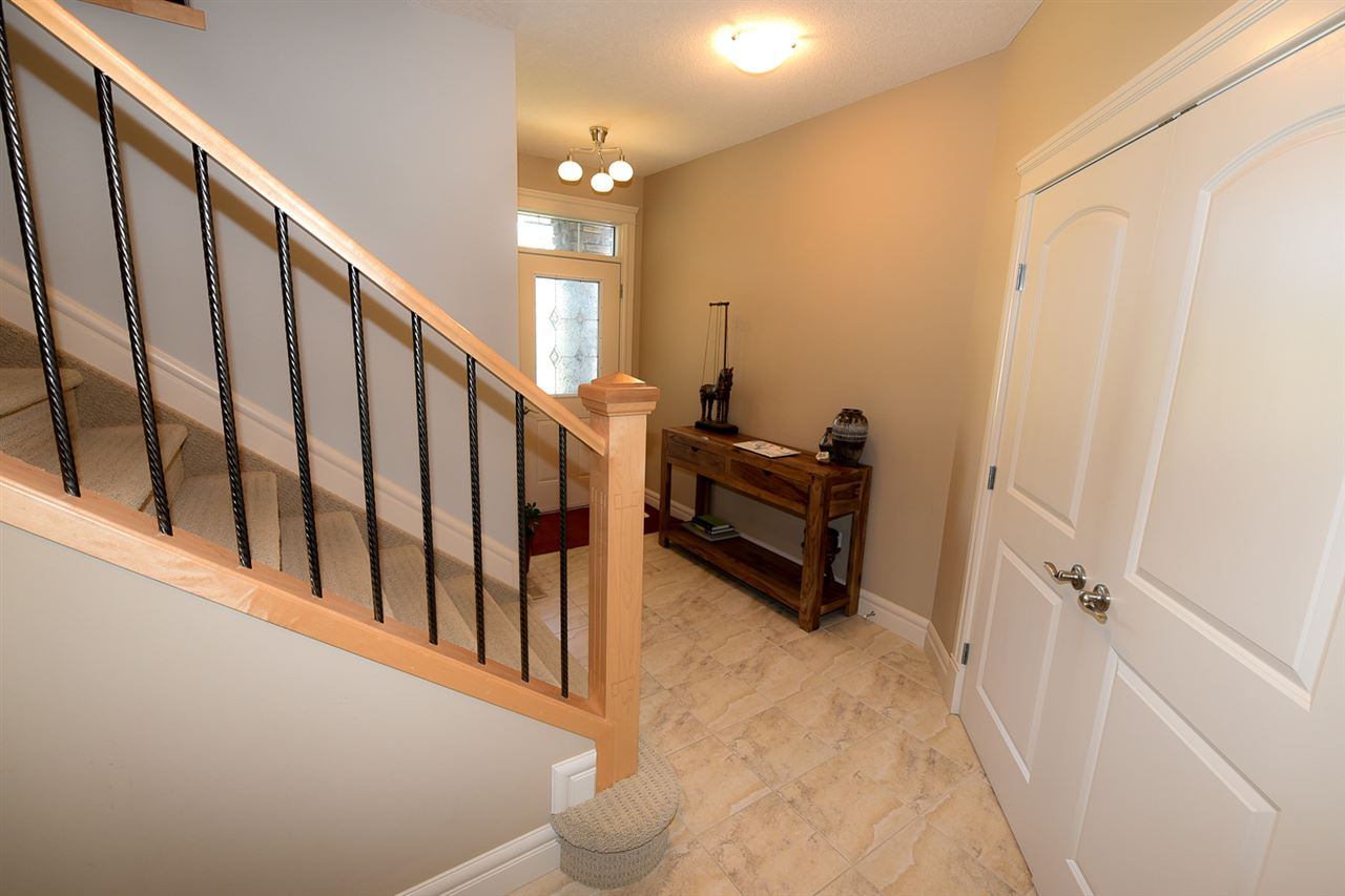 Note the wood and metal railings leading upstairs and the double doors to the front closet.