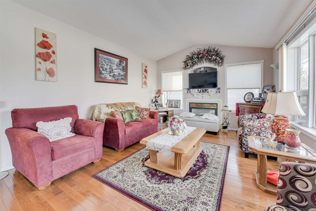 Bright living room has hardwood floors and gas fireplace