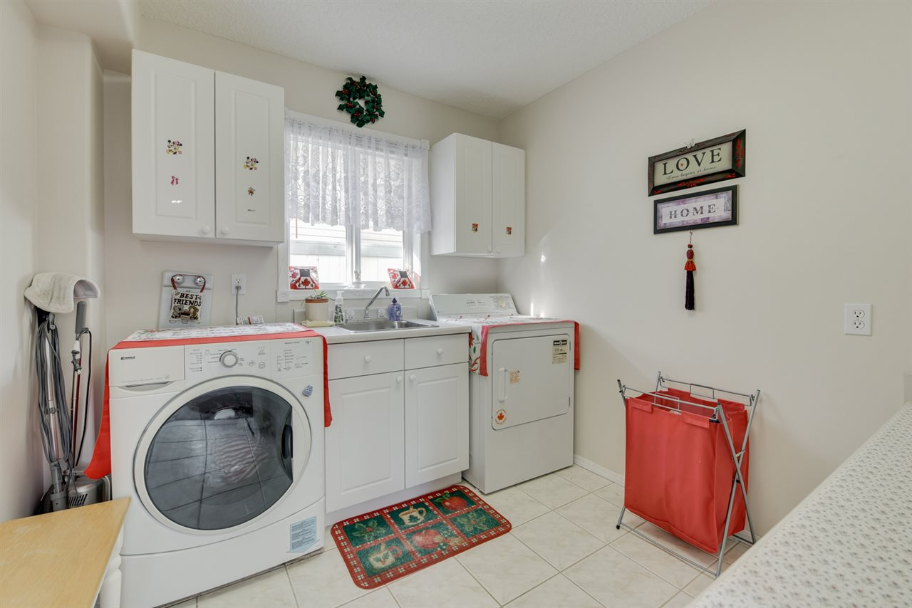 Laundry room with built in cupboards and sink
