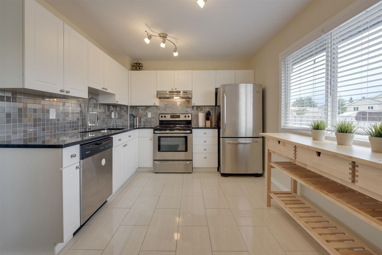 A dining area leads you into a LARGE kitchen with granite counters, stainless steel appliances, and modern backsplash.