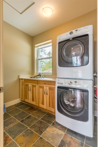 Well designed Laundry Room with a sink and custom quartz counter top.  Plenty of additional storage!
