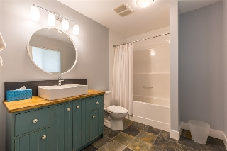 Lower level bathroom with a custom vanity piece by Dave Coyle Reproductions. Plenty of room for additional storage.